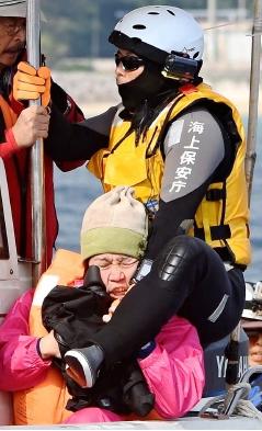 抗議船上で、カメラを持つ女性に馬乗りになる海上保安官