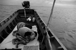 漁の手を止め、メッカを拝むムスリムの父子
