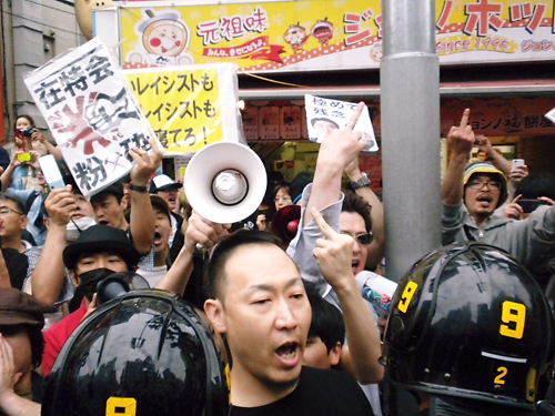 """デモを妨害している「レイシストしばき隊」の多くは、中指を立て""""Fuck you!"""" つまり、相手を「ぶっ殺すぞ」とデモ参加者たちを罵る行為を盛んに繰り返し、更に「お前ら、くたばれ!」とか「全員死ね!」とか「お前ら"""