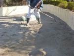 レーキで砂を集める